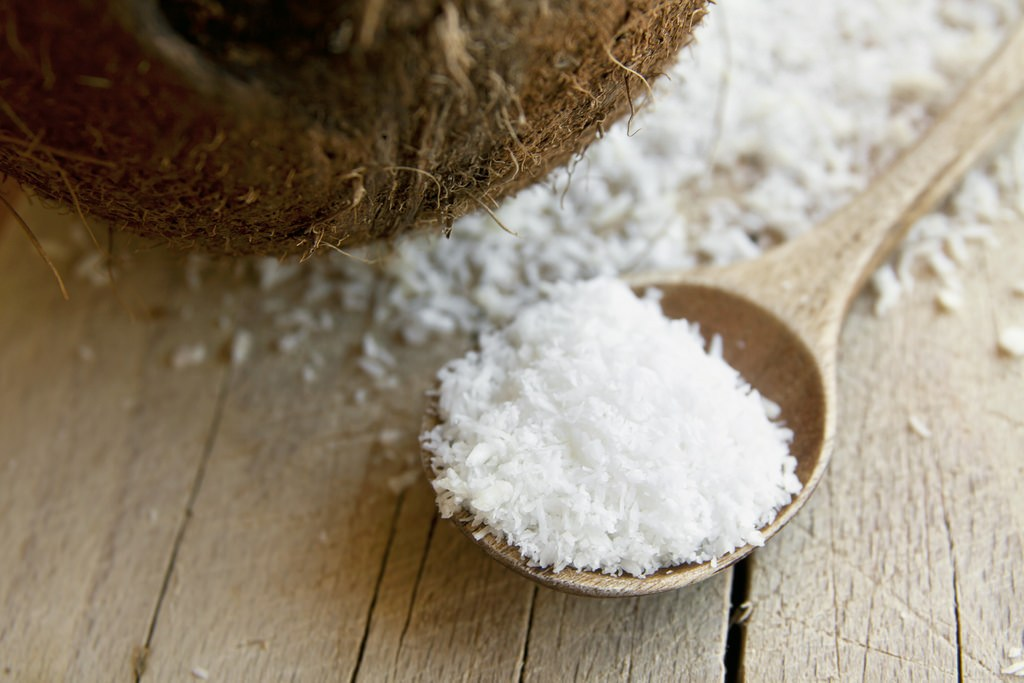 desiccated coconut on wooden spoon